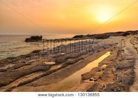 Cyprus rocky beach at golden sunset in Mediterranean sea