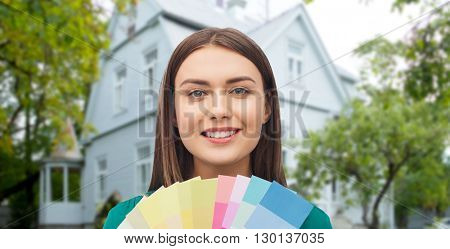 repair, renovation, decoration, design and people concept - smiling young woman with color swatches or samples over home background