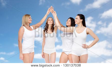 gesture, friendship, beauty, body positive and people concept - group of happy different women in white underwear making high five over blue sky and clouds background