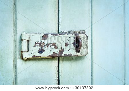 Close up of rusted keyhole on blue wooden door