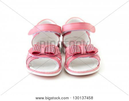 tiny pink sandals with bow isolated on white background