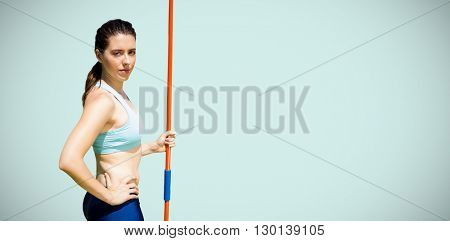 Portrait of serious sportswoman holding a javelin against blue background