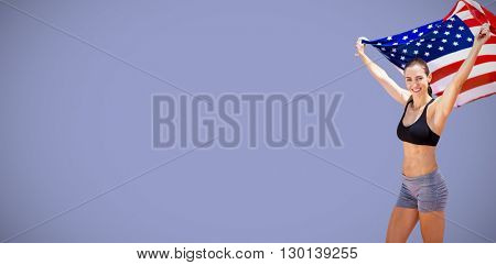 Portrait of happy sportswoman raising an american flag against purple