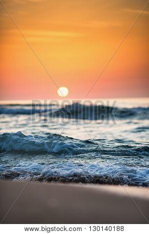 Beautiful sunrise wave and rising sun, close up