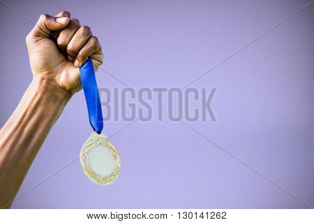 Hand holding a silver medal on white background against purple background