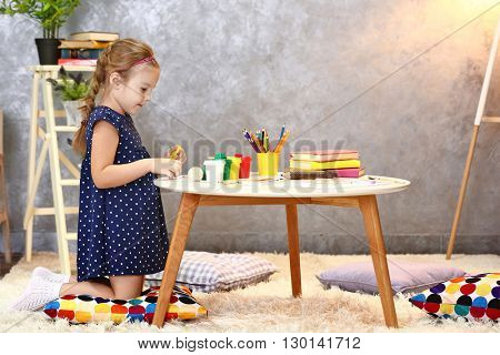 Beautiful small girl playing with plasticine
