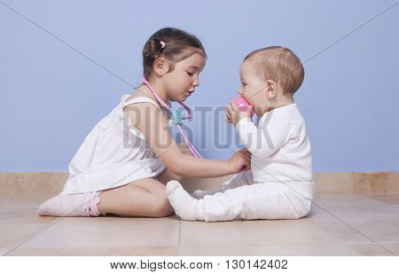 Baby brother and toddler sister playing doctor with stethoscope