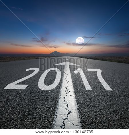 Driving on an empty road towards the setting moon to upcoming new 2017 year. Concept for success and passing time.