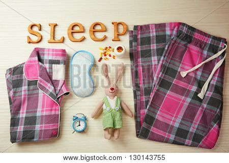 Insomnia concept. Sleeping accessories on light wooden table, top view