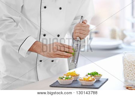 Male hands decorating fruit tarts with lime zest