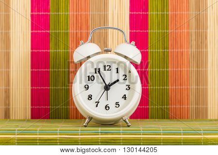 Table clock on background of decorative coloured bars of thin bamboo sticks