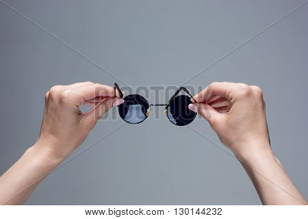 The female hands holding pair of sunglasses on gray background.