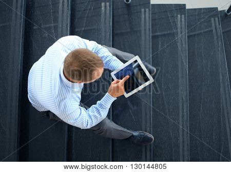 businessman sitting on stairs and using electronic tablet