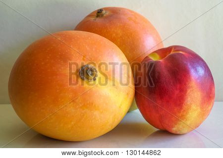 Two ripe golden-orange mangoes with a ripe red and yellow nectarine.