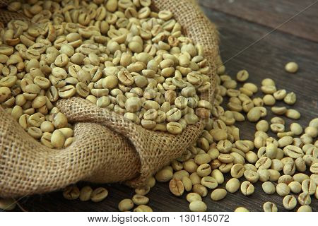 Raw coffee beans in gunny sack over old dark wooden table