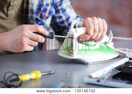 Young man fixing an iron in repair center