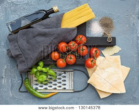 Ingredients for cooking pasta. Spaghetti on dark wooden board, Parmesan cheese, cherry tomatoes, metal grater, olive oil and fresh basil on grey concrete background, top view