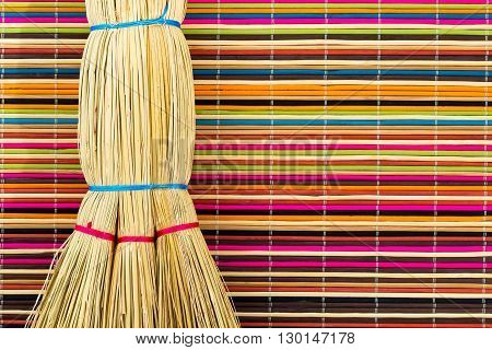Broom tied with bright ropes on motley multicolored background of bamboo sticks