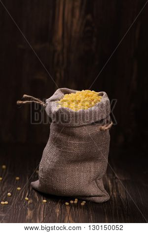 Golden pearl couscous in a burlap bag over grunge wooden background. Vintage style