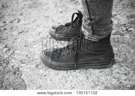 Teenager Feet In Black Gumshoes And Jeans