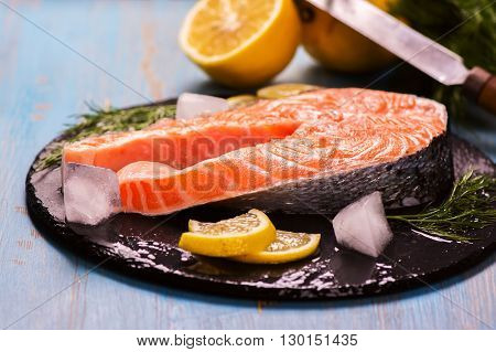 Raw salmon steak with lemon and herbs over wooden background. Healthy food concept