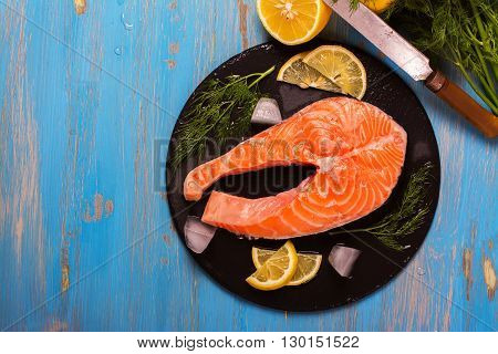 Raw salmon steaks and ingredients on slate background. Selective focus. Top view