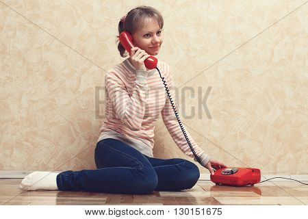 Girl sitting on the floor near the wall and calling on the red phone