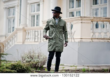 Fashion Portrait Of Black African American Man On Green Coat Cloak And Black Hat, Background Yellow