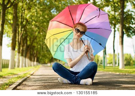 Girl in sunglasses and with colorful umbrella is sitting on sidewalk in bright sunny summer day