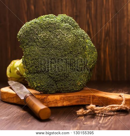 Fresh whole raw broccoli cabbage with vintage knife over grunge wooden table. Selective focus