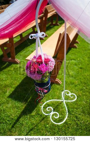 Wedding decoration of flowers near benches for ceremony in park.