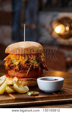 Pulled pork BBQ burger with tomatoes and jalapeno, selected focus