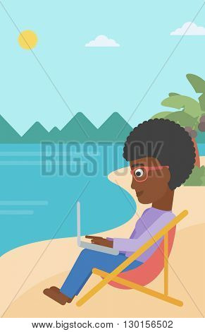 Business woman sitting in chaise lounge with laptop.