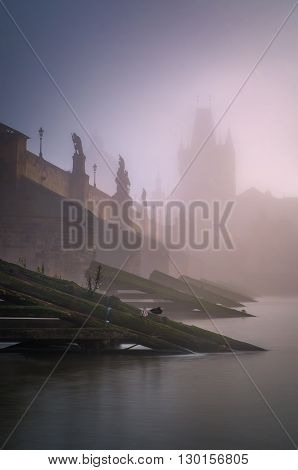 Foggy day near Charles bridge with reflection at Vltava river Prague Czech republic