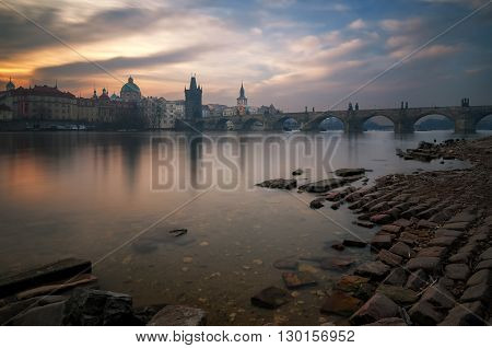 Cloudy sunrise near Charles bridge with reflection at Vltava river Prague Czech republic