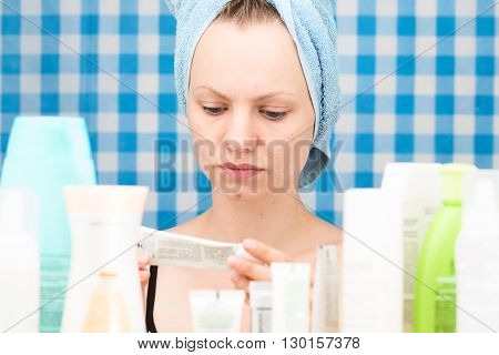 Girl is reading inscription on cosmetic product in bathroom
