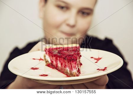 Joyful caucasian boy posing with the piece of cheesecake with raspberries. Sweet food theme.
