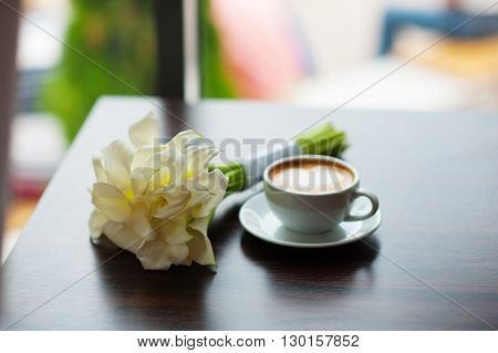 cup of coffee and a bouquet of flowers on a table in a cafe.