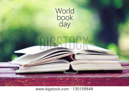 Open books on bench in park. World Book Day poster
