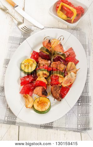 grilled hungarian pork red pepper onion and courgette skewers on an white oval plate