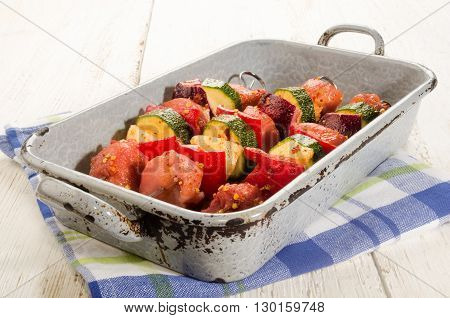 marinated hungarian pork and vegetable skewers in a rustic roasting tray