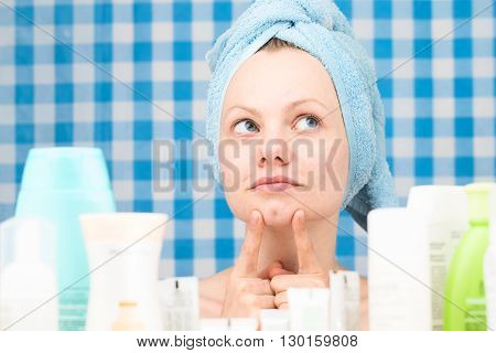 Girl with towel on her head is smiling surrounded by various cosmetics in bathroom