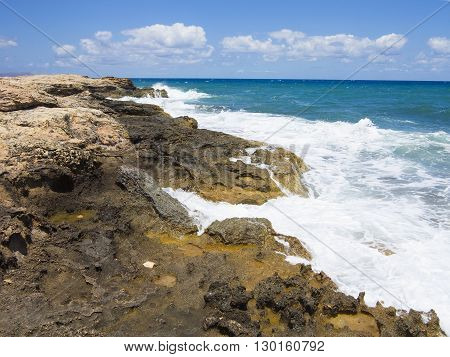 Big waves on rock coast blue sea and sky on Crete Greece