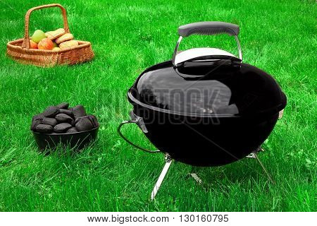 Bbq Grill Appliance, Charcoal Briquettes And Tools On The Lawn