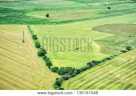Green fields and high voltage power lines view from airplane. Seasonal natural scene. Agricultural theme. European country.