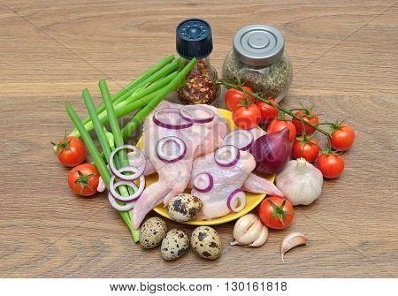 raw chicken wings vegetables and quail egg on a wooden background. horizontal photo.