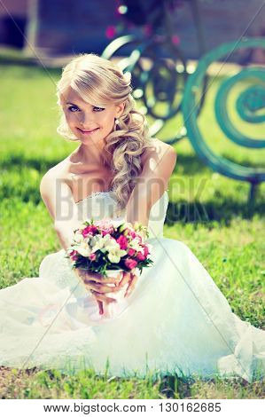 eautiful blonde bride  girl with wedding  bouquet of flowers