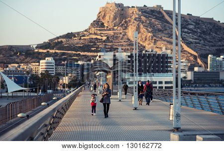 Alicante Spain-February 24 2016: People walking on the Alicante pier. View to the Santa Barbara castle. Castle one of the most well-known landmarks in Alicante and the most visited. Valencian Community Spain