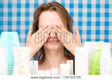 Young girl with problem skin is closed her eyes in front of set of cosmetics in bathroom. Skin care and beauty concept. Frontal portrait