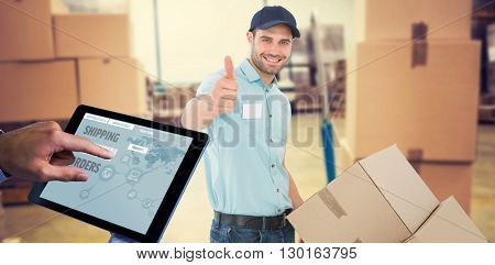 Man using tablet pc against boxes on trolley in warehouse